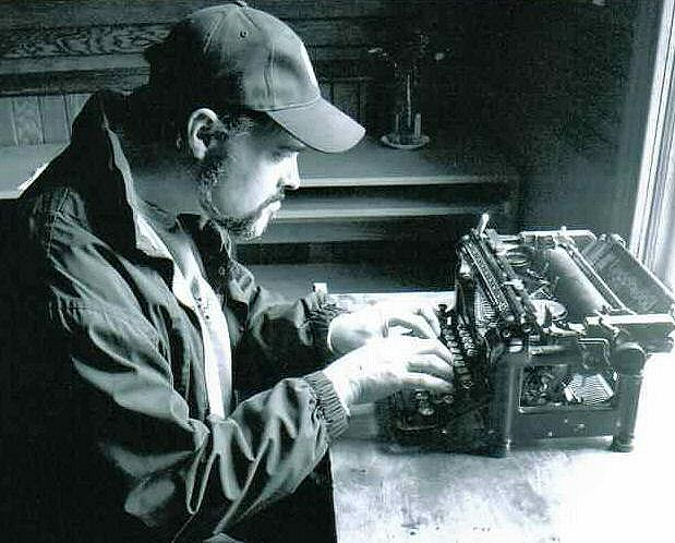 Man in a cap typing on a tiny, very old typewriter