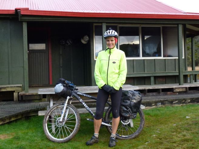Jenny Cossey, mountain biker, outside one of the 50 NZ mountain huts on her bucket list
