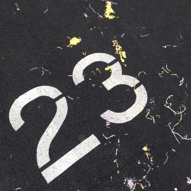 Number 23 painted in white on asphalt, with white and yellow paint squiggles.