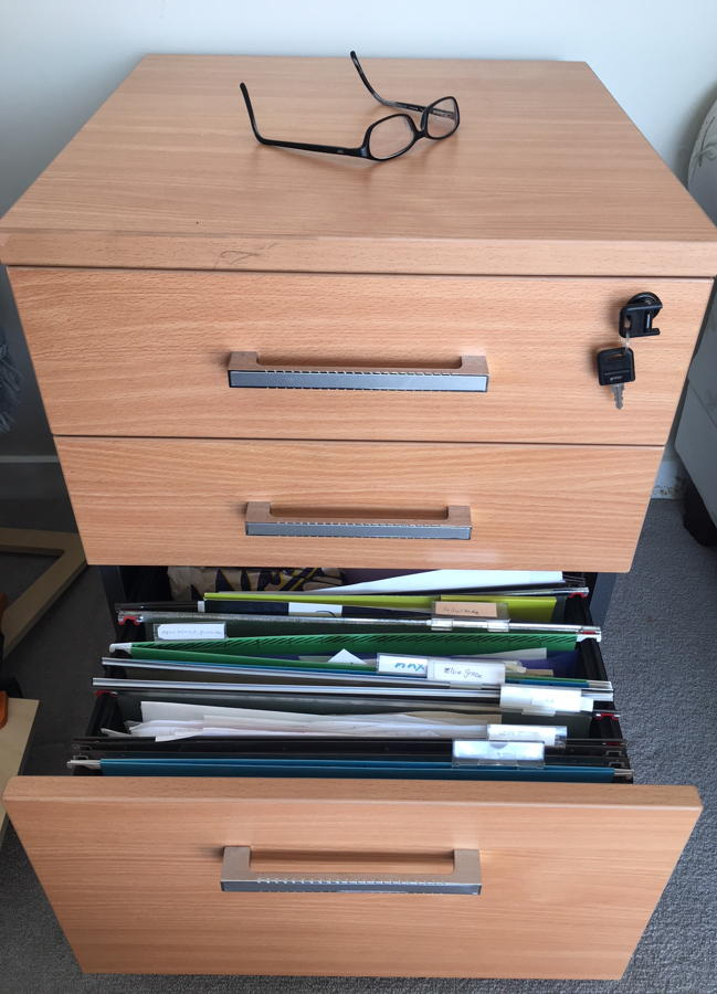 Spectacles on a small filing cabinet that reveals untidy files.
