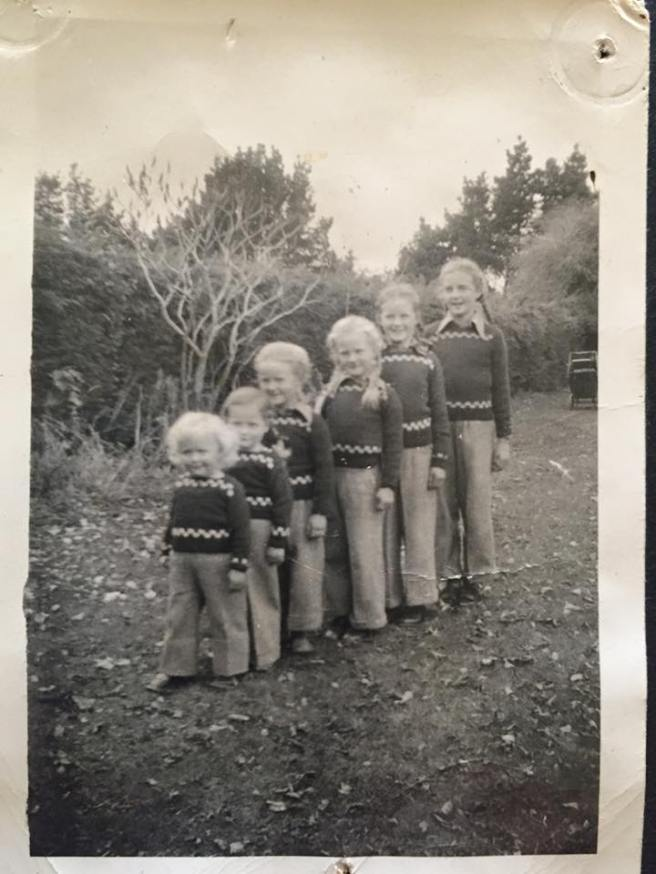 6 girls in plaits, slacks and hand-knitted jerseys