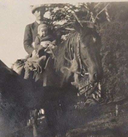 Rev. David Taylor on horseback with toddler in front.