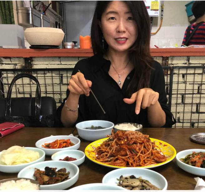 Junghee points to lunch of seafood and sprouts with Korean side dishes.