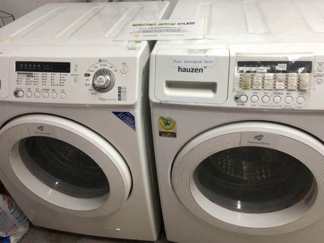 Two washing machines, one with instructions in Korean, the other in English